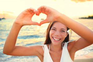 Love vacation - woman showing heart on beach. Girl gesturing heart shaped hands smiling happy and loving at camera. Pretty joyful multicultural Asian Caucasian girl.